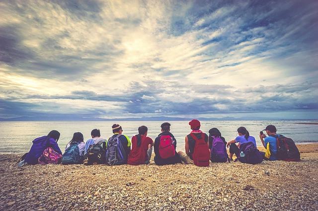 Groupe enfant de dos assis sur une plage